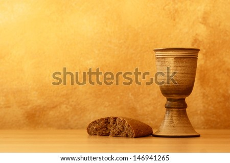 Chalice with wine and bread. Background with copy space. - stock photo