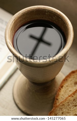 Chalice with wine, piece of bread and open Bible. - stock photo