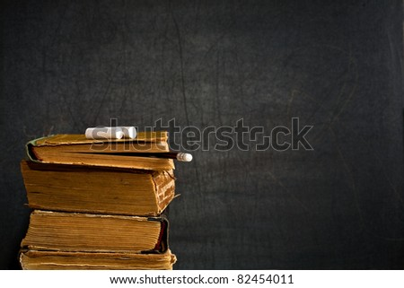 Chalk and pencil on old textbook against blackboard in class. School concept - stock photo