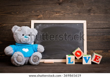 chalk board and  teddy bear on a wooden background - stock photo