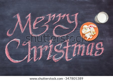 Chalk board with Merry Christmas message , cakes on background for a greeting card - stock photo