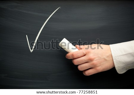 chalk tick and hand against blackboard background