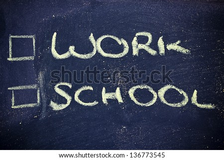 chalk writings on blackboard, choice between work and school - stock photo