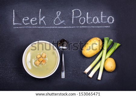 Chalkboard advertising the soup of the day, with a bowl of leek and potato soup and spoon, garnished with bread croutons, with leeks and potatoes on the side - stock photo
