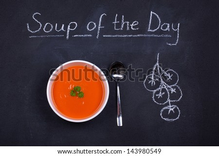 Chalkboard advertising the soup of the day, with a bowl of tomato soup and spoon, garnished with parsley, with chalk drawn tomatoes on the side - stock photo