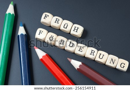 Chalkboard and the german words early support / Child education - stock photo