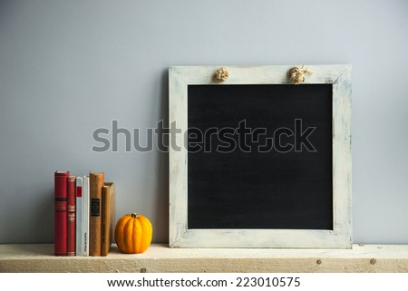 chalkboard frame on the grey wall with books and pumpkin. scandinavian style interior - stock photo