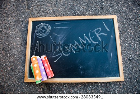 Chalkboard on asphalt that has summer written on it and a sun with colorful street chalk - stock photo