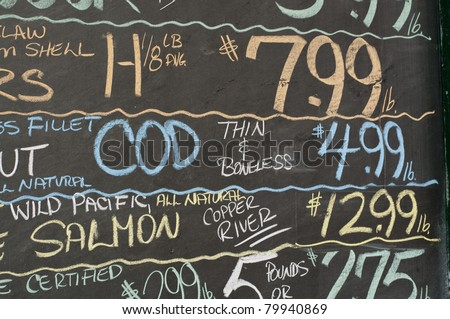 Chalkboard shows the prices of the day's fish catch outside a market in Portland, Maine. - stock photo
