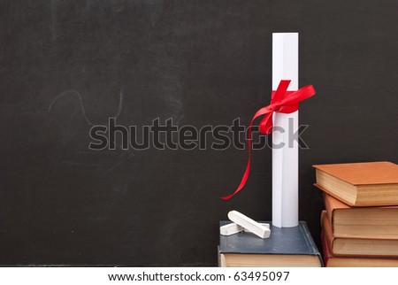 Chalkboard with a diploma and books - stock photo