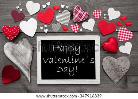 Chalkboard With English Text Happy Valentines Day. Many Red Textile Hearts. Wooden Background With Vintage, Rustic Or Retro Style. Black And White Image With Colored Hot Spots. - stock photo