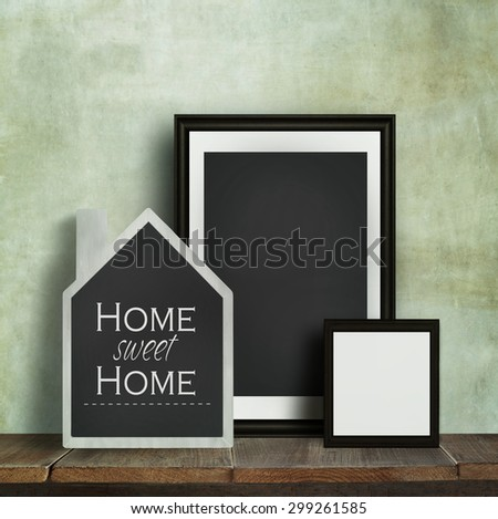 Chalkboard with quote and frames on old table - stock photo