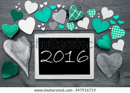 Chalkboard With Text 2016 For New Years Greetings. Many Green Textile Hearts. Wooden Background With Vintage, Rustic Or Retro Style. Black And White Image With Colored Hot Spots. - stock photo
