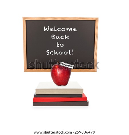 Chalkboard with the words Welcome Back to School with a pile of books and an apple for the teacher.   - stock photo
