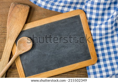 Chalkboard with wooden spoons on a blue checkered tablecloth - stock photo