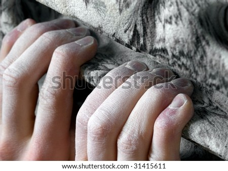 Chalked fingers hang off an artificial climbing hold. Shallow depth of field - stock photo