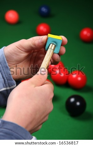 Chalking the end of a cue for a snooker game - stock photo