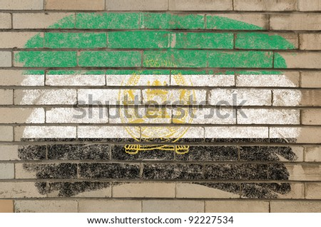 Chalky afghan flag painted with color chalk on grunge old brick wall - stock photo