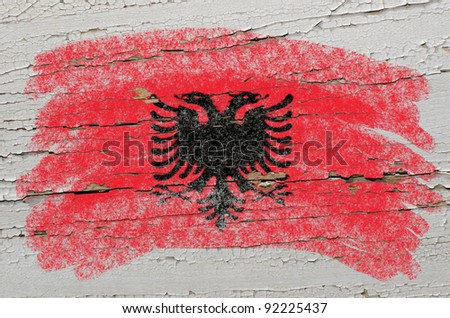 Chalky albanian flag painted with color chalk on grunge wooden texture - stock photo