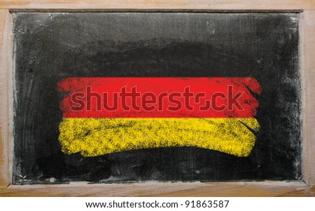 Chalky german flag painted with color chalk on old blackboard - stock photo
