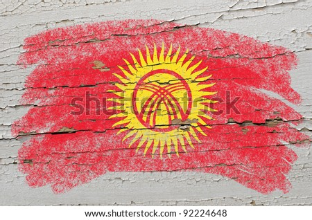 Chalky kyrghyzstan flag painted with color chalk on grunge wooden texture - stock photo