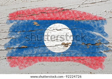 Chalky laos flag painted with color chalk on grunge wooden texture - stock photo