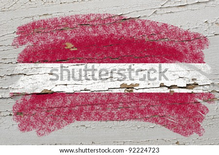 Chalky latvian flag painted with color chalk on grunge wooden texture - stock photo