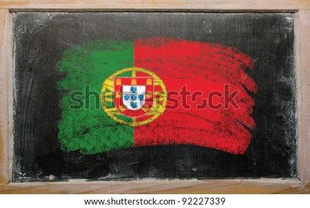 Chalky portugese flag painted with color chalk on old blackboard - stock photo