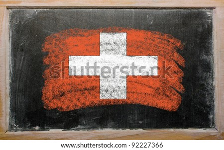 Chalky swiss flag painted with color chalk on old blackboard - stock photo