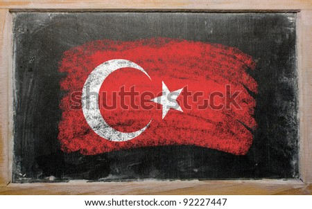 Chalky turkish flag painted with color chalk on old blackboard - stock photo