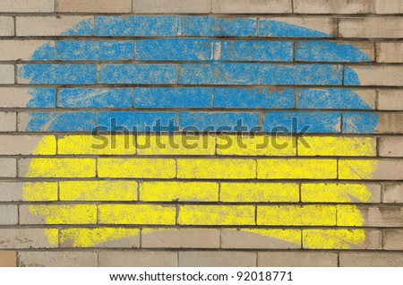 Chalky ukrainian flag painted with color chalk on grunge old brick wall - stock photo