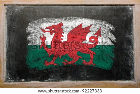 Chalky welsh flag painted with color chalk on old blackboard - stock photo