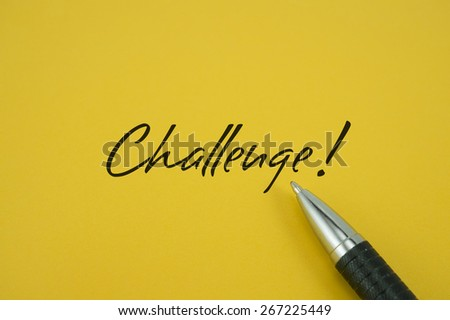 Challenge! note with pen on yellow background - stock photo
