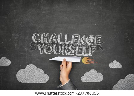 Challenge yourself concept on black blackboard with businessman hand holding paper plane - stock photo