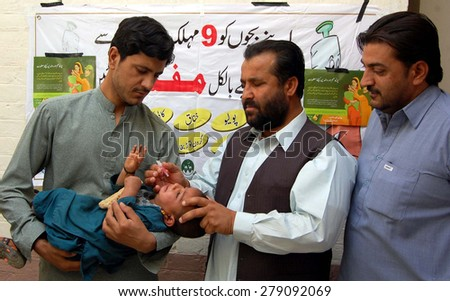 CHAMAN, PAKISTAN - MAY 18: Deputy Commissioner administrates polio-vaccine drops to a child during the inauguration ceremony of anti-polio immunization campaign on May 18, 2015 in Chaman.  - stock photo