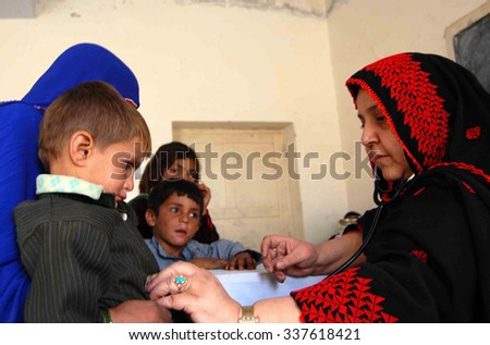 CHAMAN, PAKISTAN - NOV 10: Frontier Corps commander Major Umar distributing free books and gifts packs among children during free medical camp, on November 10, 2015 in Chaman.