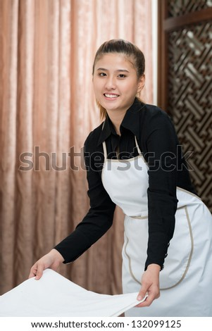 Chamber maid working and looking at camera - stock photo