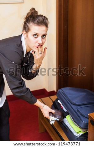 Chambermaid Stealing Money from Bag - stock photo