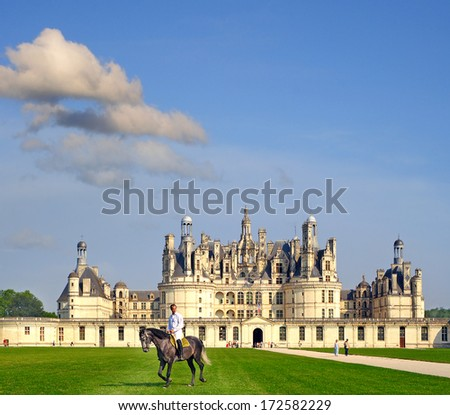 CHAMBORD, FRANCE - JULY 16: Rider on horseback in front of the chateau Chambord on July 16, 2005. Chambord is royal medieval french castle in Loire Valley - UNESCO heritage site. - stock photo