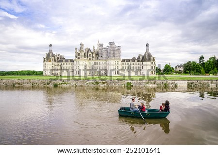 CHAMBORD, FRANCE -MAY 29: Family on a boat in front of the chateau Chambord on May 29, 2014. Chambord is royal medieval french castle in Loire Valley - UNESCO heritage site. - stock photo