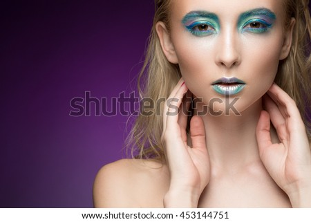 Chameleon sensuality. Closeup shot of a stunning female model wearing professional colorful metallic makeup touching her face sensually looking to the camera