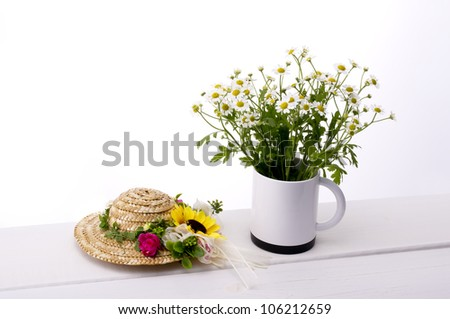chamomile flower in cup straw hat on table - stock photo