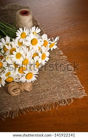 Chamomile flower on coarse napkin on wooden background - stock photo