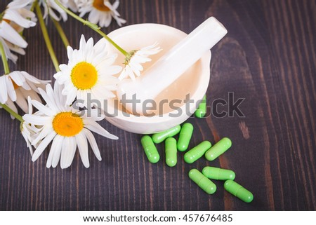 Chamomile flowers and green phytotherapeutic capsules on a wooden table. Herbal medicine and health - stock photo