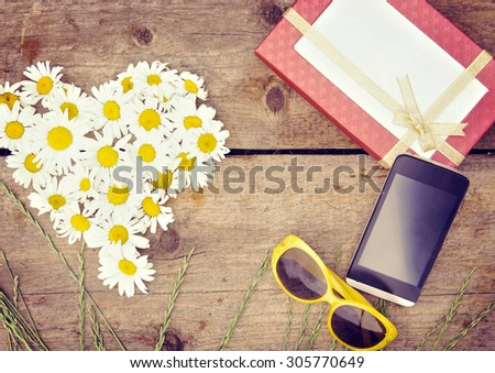 Chamomile flowers as a shape of heart with gift box and smartphone lie on wooden surface. Toned image - stock photo