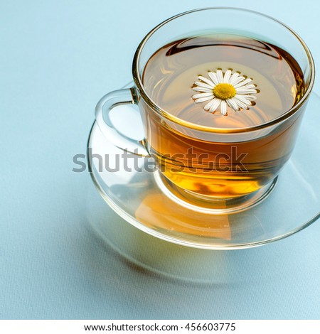 Chamomile tea in glass Cup and saucer. Herbal tea. Alternative medicine. Blue background. Live chamomile. Flower in a Cup of tea. Relaxation and rest. Calm the nervous system.