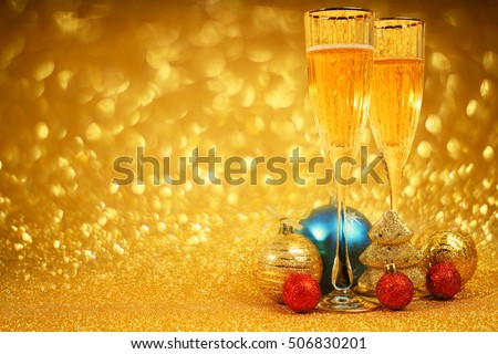 Champagne and christmas decor on golden glitter background with copy space