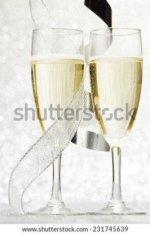Champagne and gift ribbon on silver bokeh background