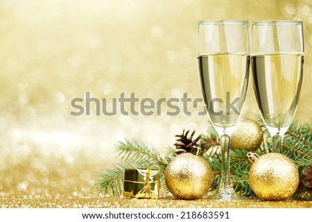 Champagne and new year decorations on golden background - stock photo