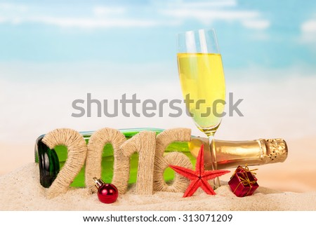Champagne and New year 2016 sign on sandy beach - stock photo